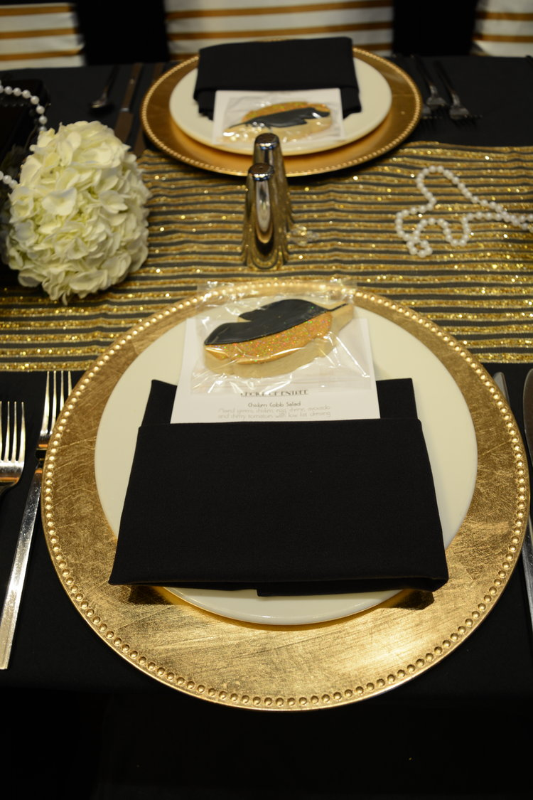 Overhead view of plate, place setting, and a feather cookie favor with rehearsal dinner menu