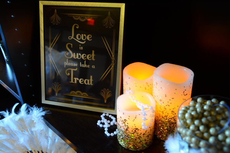 "Closeup view of glittery candles with a ""Love is Sweet please take a Treat"" signage"
