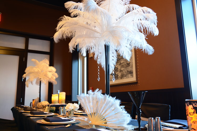 Another look at ostrich feather table centerpieces with various place settings in gold, black, and navy theme