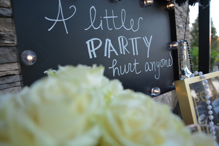 "Closeup of a chalkboard with ""A little party never hurt anyone"" message written on it"