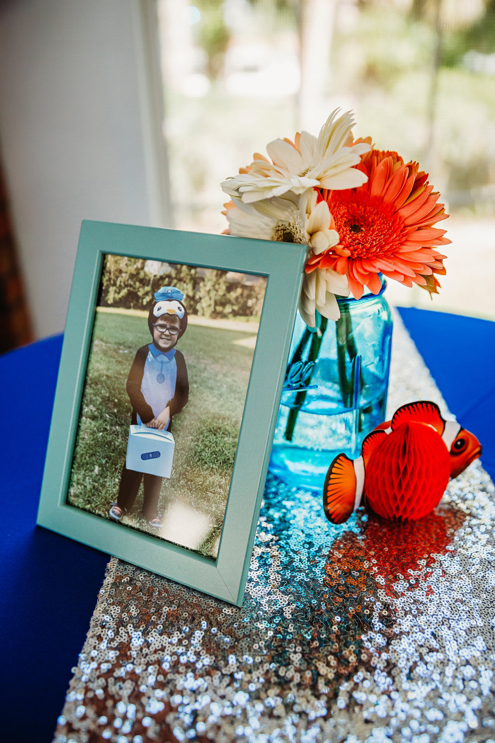 Closeup of table decoration with photo of boy dressed up as a penguin