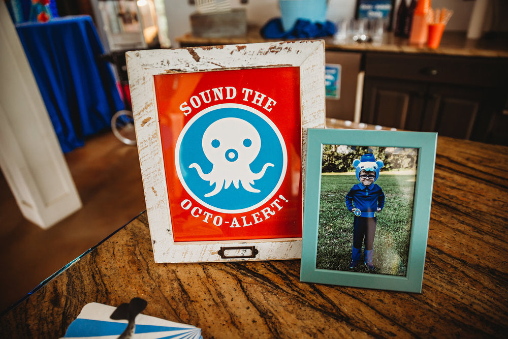 "Closeup of 2 picture frames: one with a ""Sound the Octo-Alert"" sign, and the other of a boy in a bear costume"