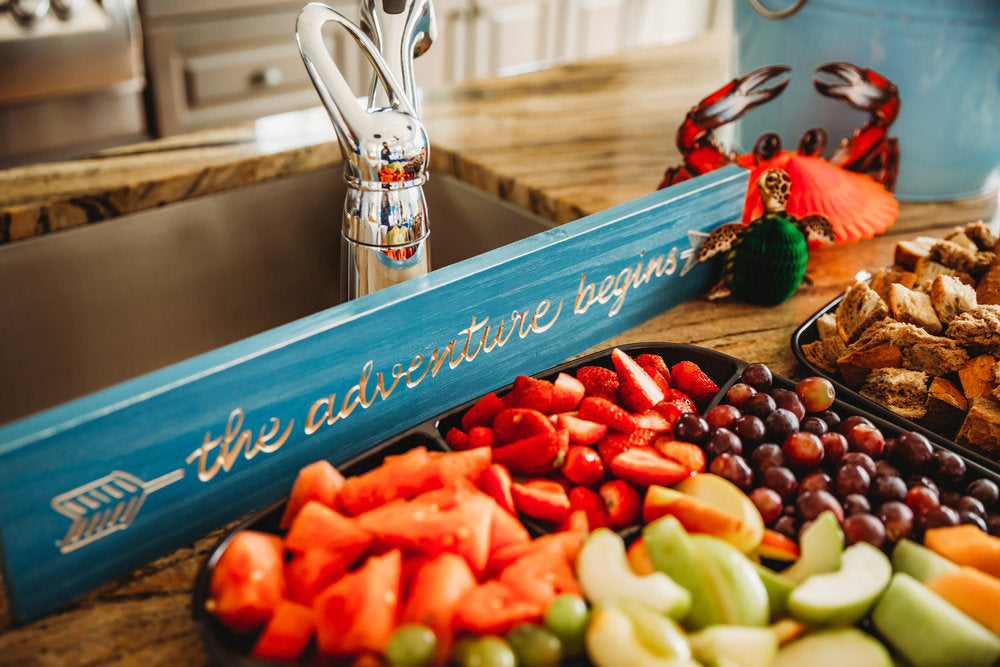 "Closeup photo of a fruit tray and ""The Adventure Begins"" sign"
