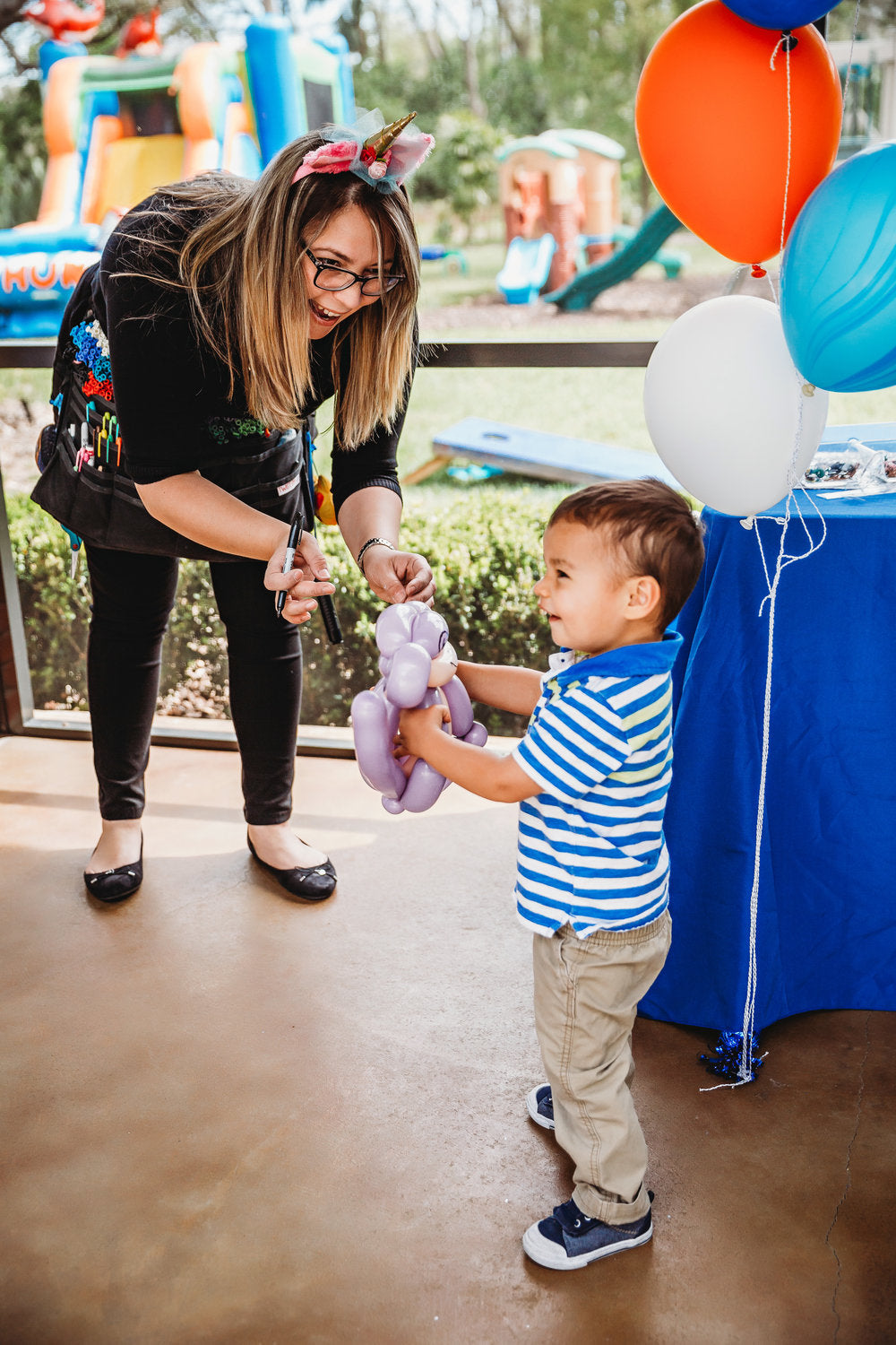 Female adult handing balloon animal to small boy