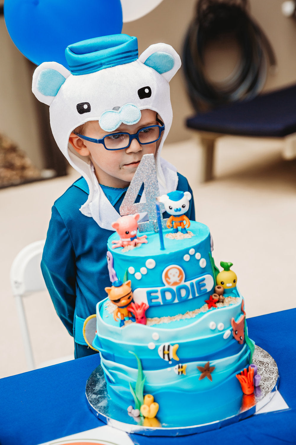 Birthday boy in front of his nautical themed birthday cake
