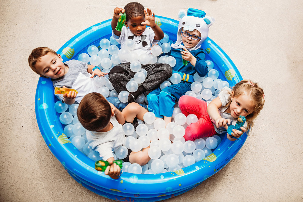 Diverse group of 5 children sitting in blow up pool filled with ball pit plastic balls