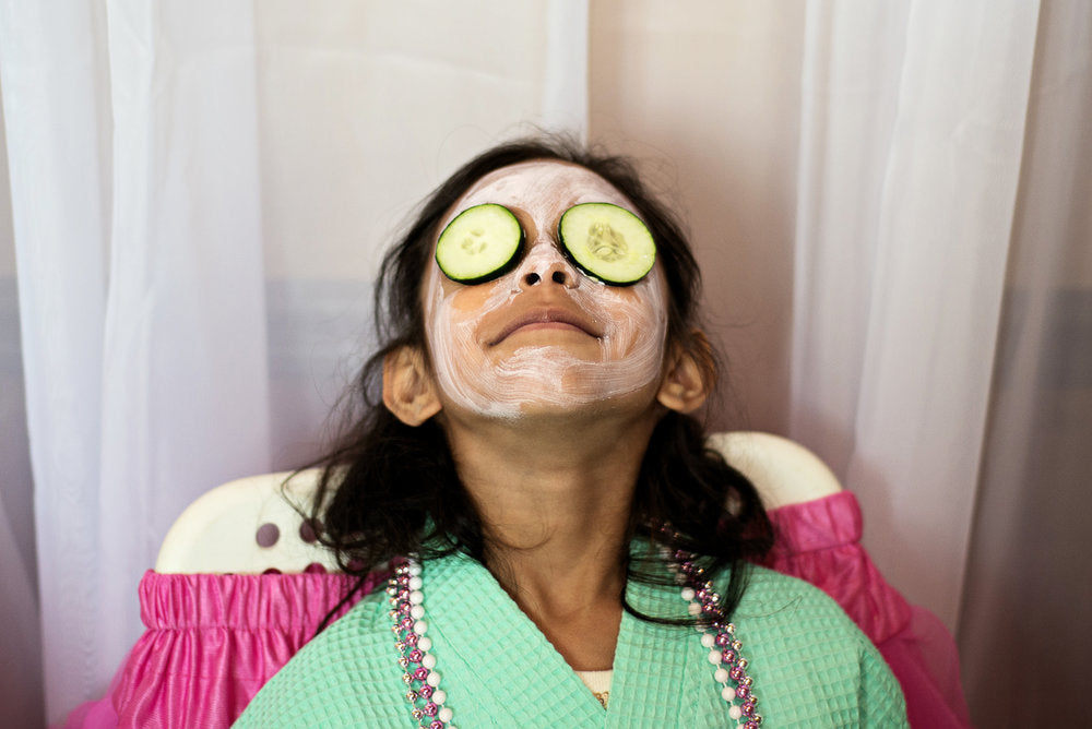 Birthday party attendee with cucumbers over her eyes relaxing with a mud mask on.