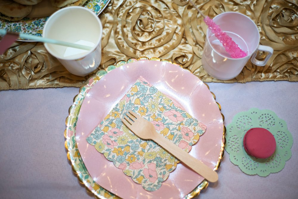 Overhead shot of table placesetting with spa themed paper plates and paper cups