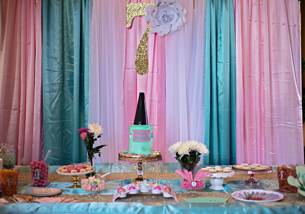 Decorated room and table holding a teal birthday cake and birthday treats