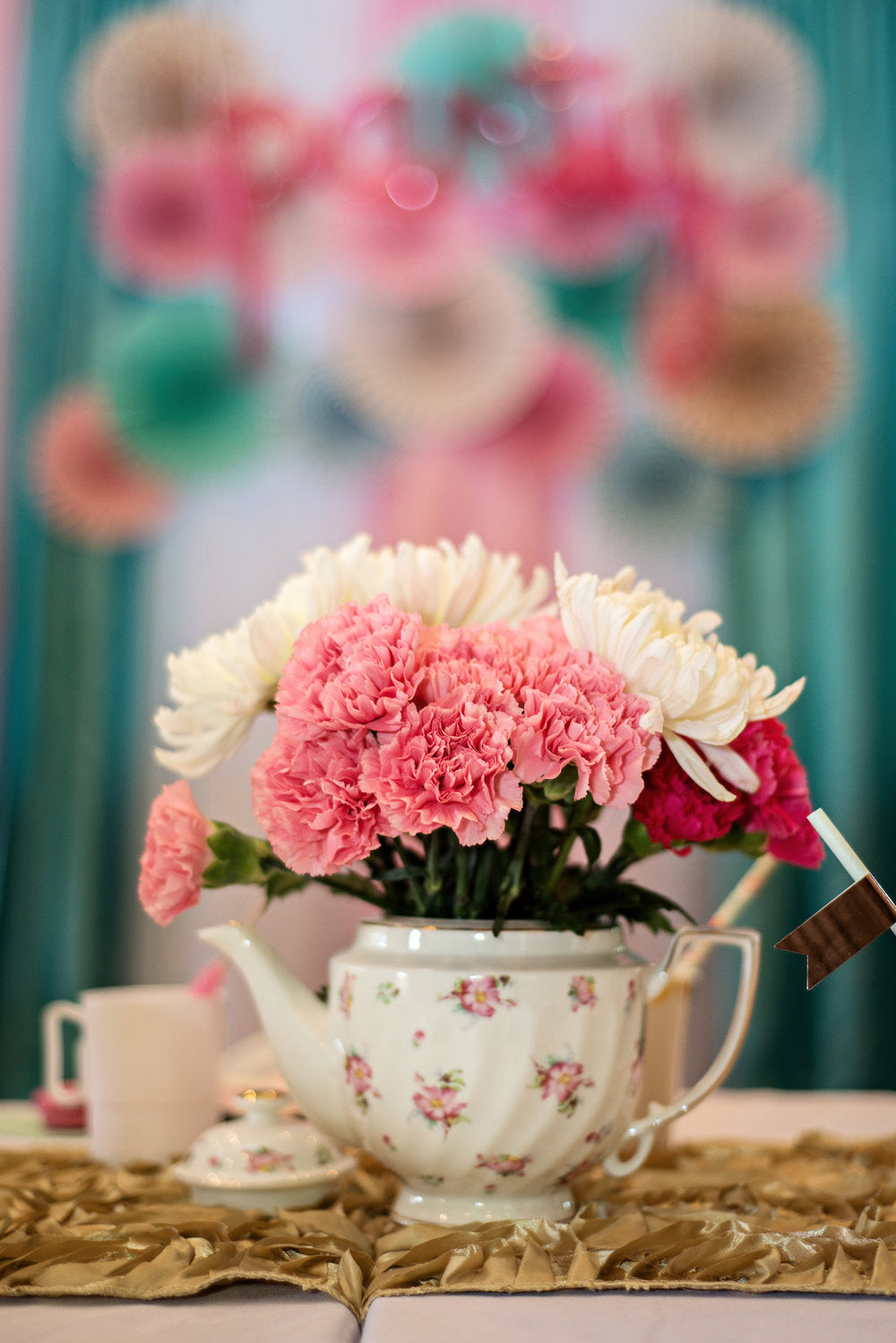 Closeup photo of flower arrangement sitting inside a teapot