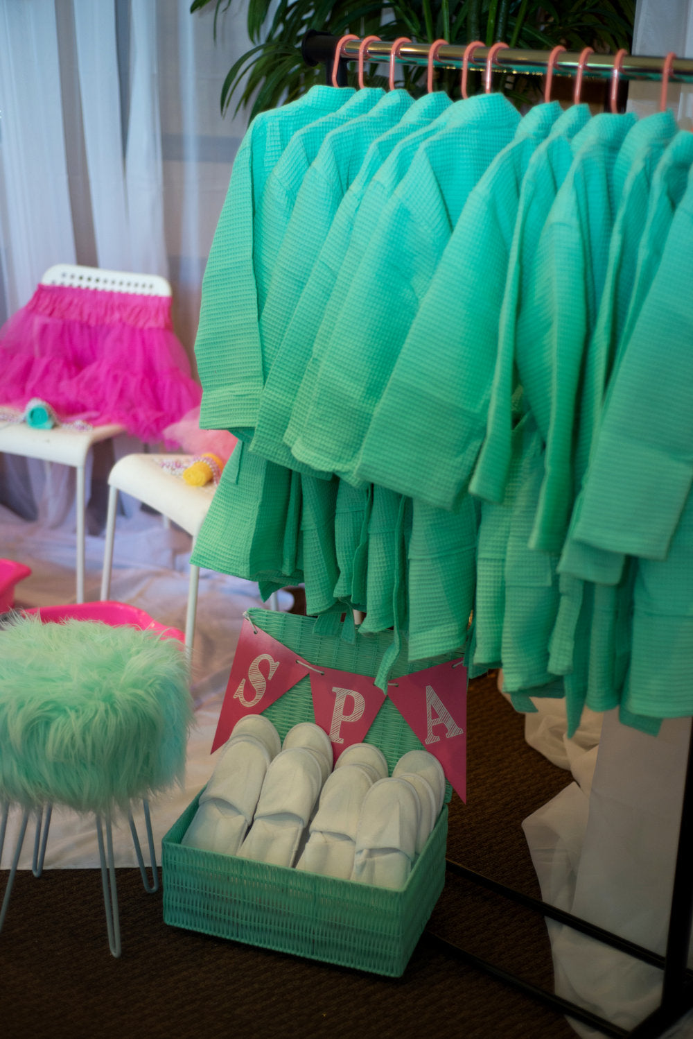 Rack of fluffy foam green spa robes and basket of white spa slippers