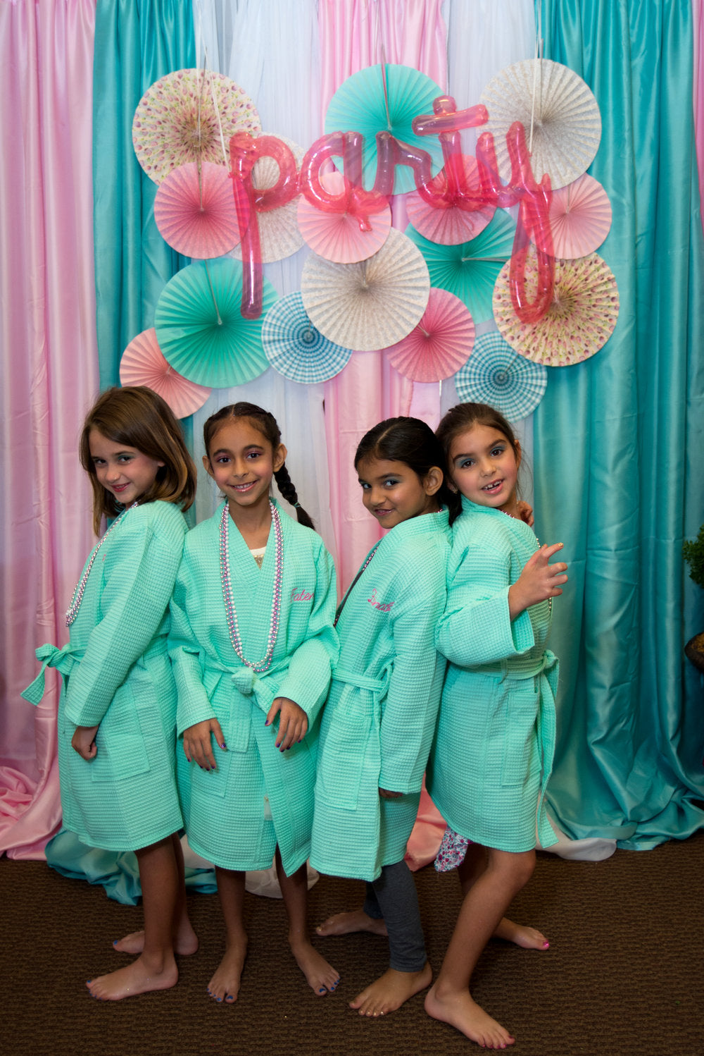 4 birthday party attendees in spa robes posing in front of party wall decorations