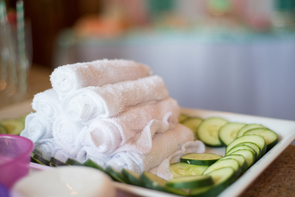 Closeup photo of white face towels and cucumber slices