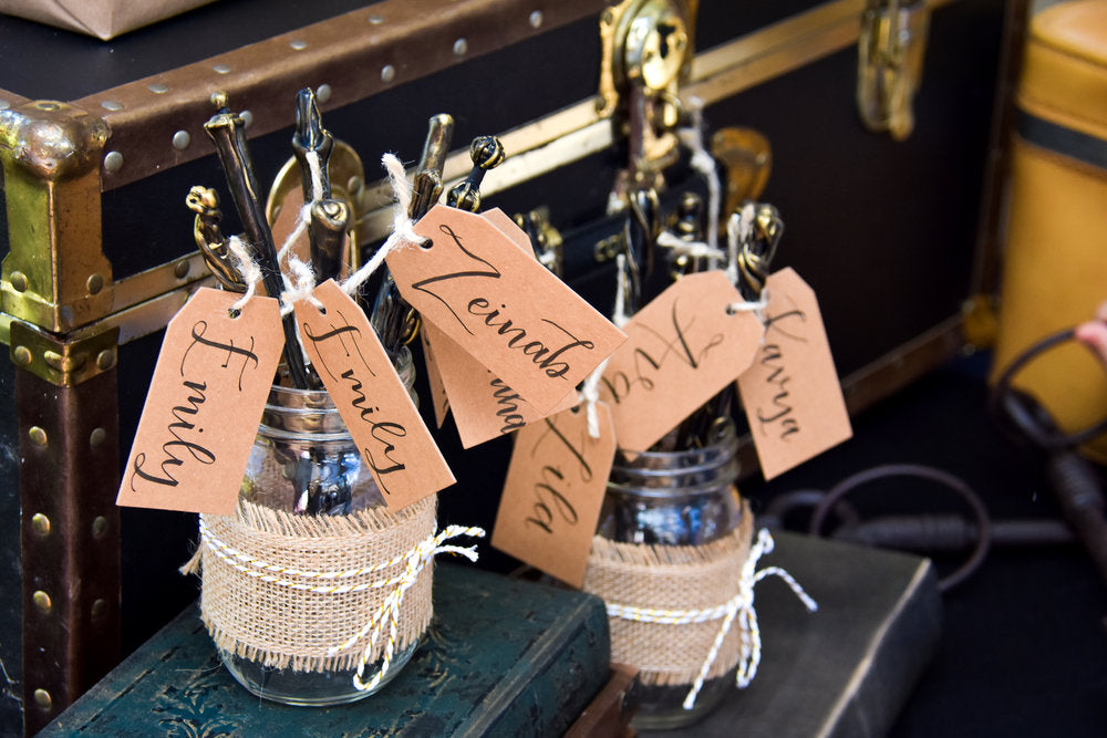 Closeup photo of guest name tags hanging from magic wands sticking out of mason jars