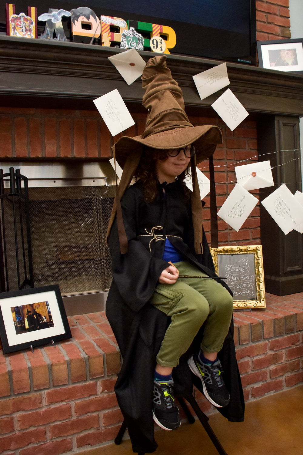 Harry Potter birthday party attendee sitting with Sorting Hat