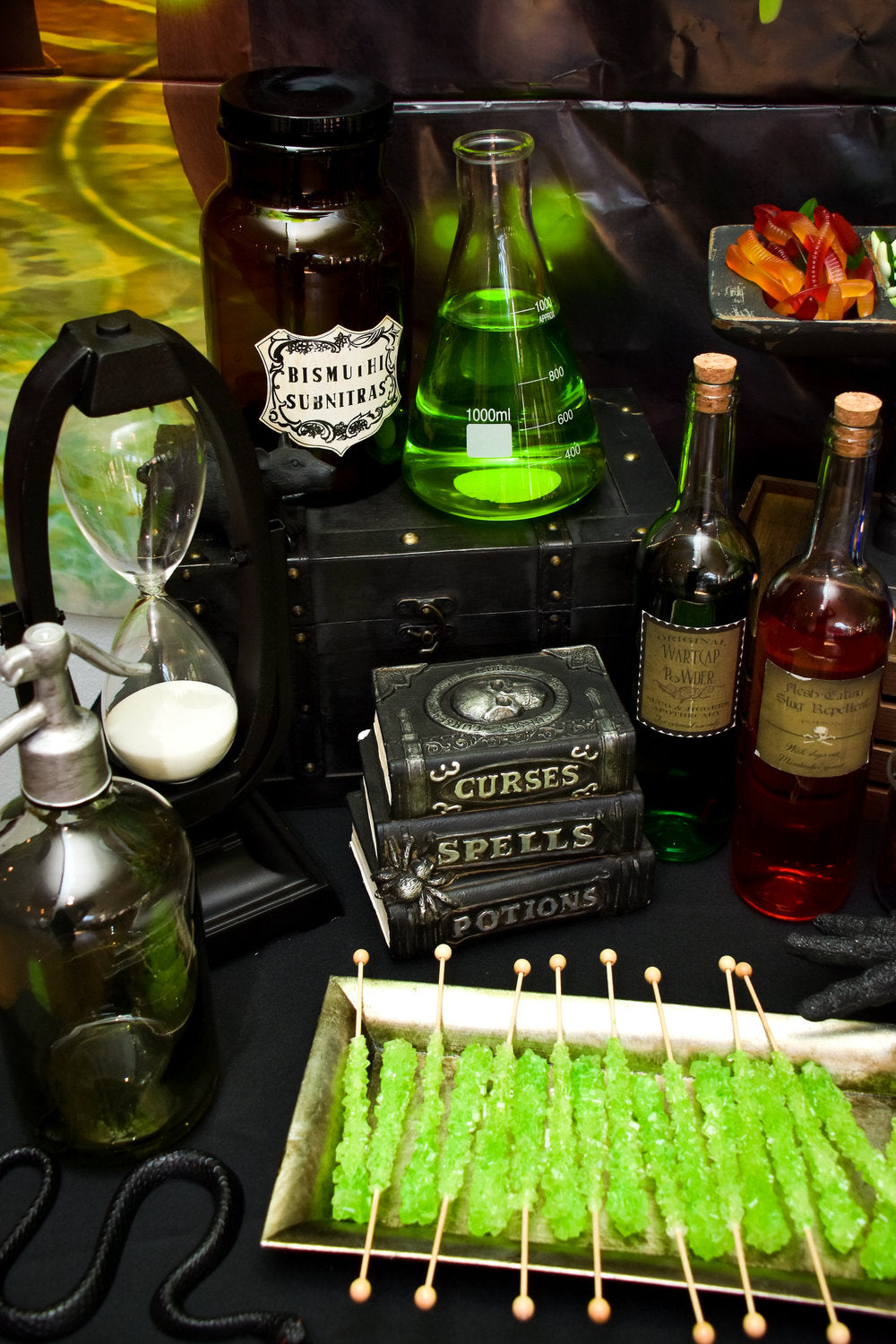 Closeup photo of potions table with green rock candy lollipops and spellbooks