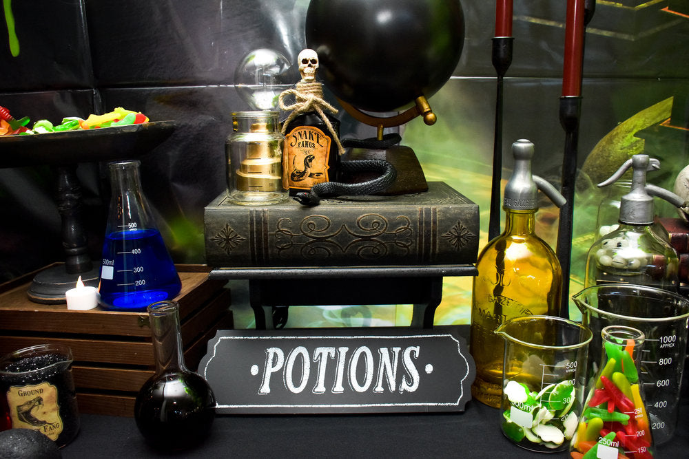 Closeup photo of potions table decorations with books, scientific equipment, and candy