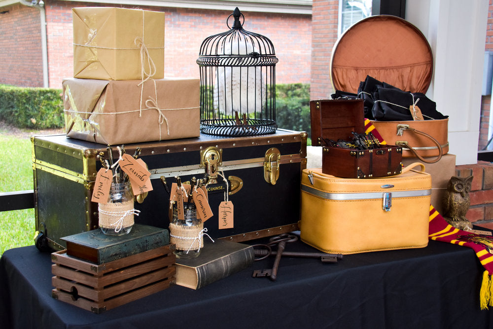 Closeup of vintage luggage boxes and a birdcage for Harry Potter themed birthday party