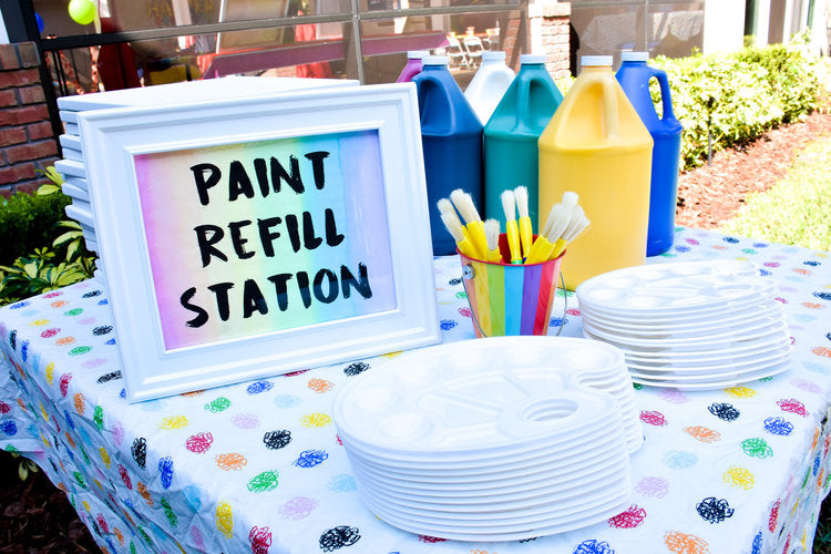 Paint refill station with white paint palettes and 6 giant jugs of tempera paint in all different colors