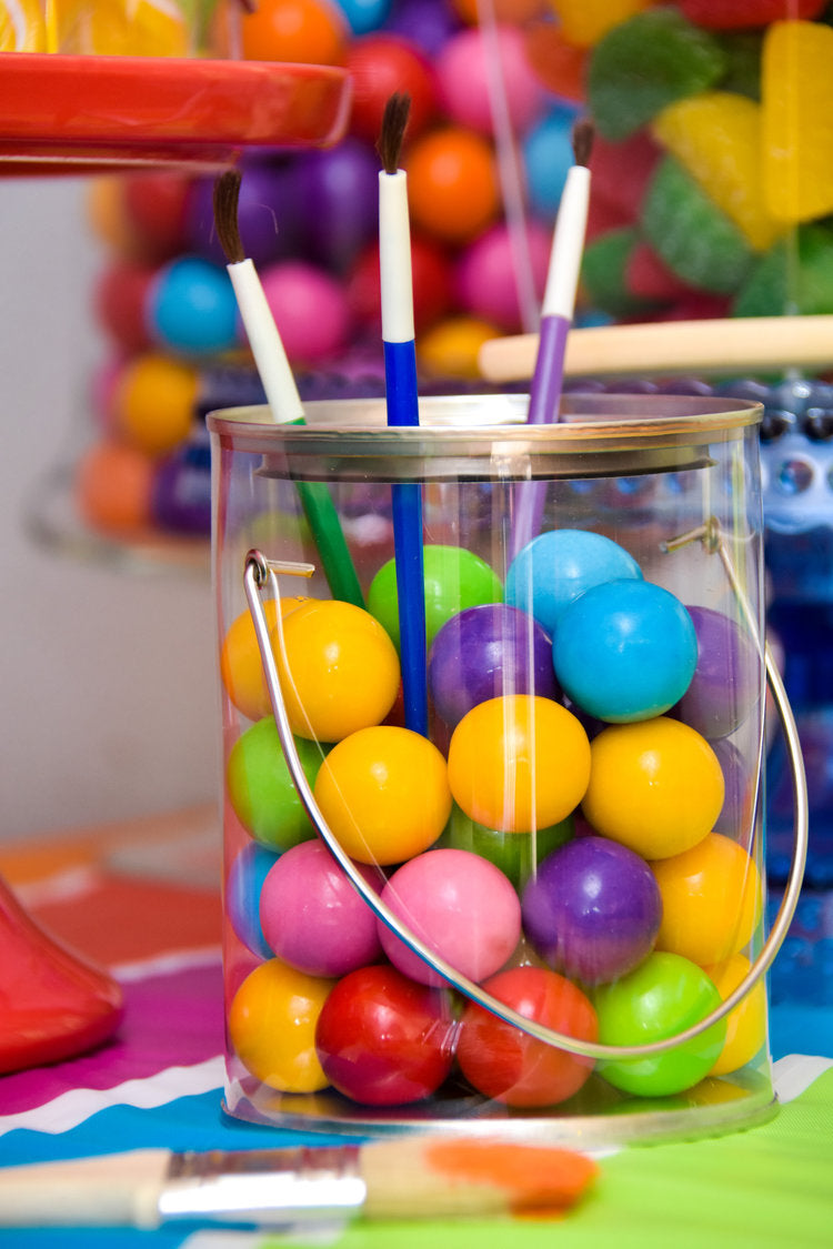 3 paintbrushes sticking out of clear paintbucket jar filled with colorful gumballs