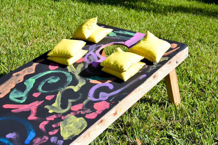 Chalk decorated cornhole boards with bean bags resting on them
