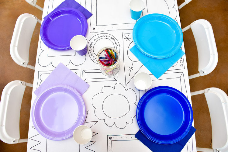 Overhead view of colorful plastic plates and cups over line drawing table cloth
