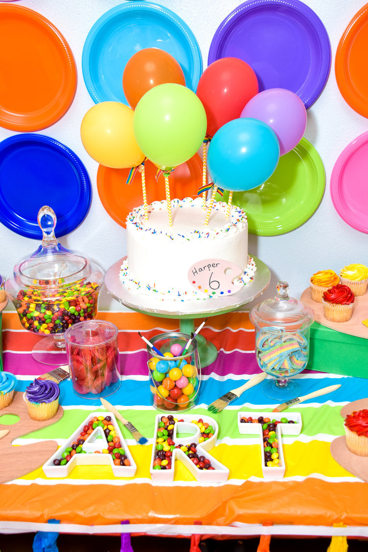 Closeup photo of white birthday cake decorated with sprinkles sitting near candy jars and cupcakes