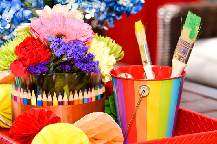 Two paintbrushes in a colorful pail next to flower centerpiece