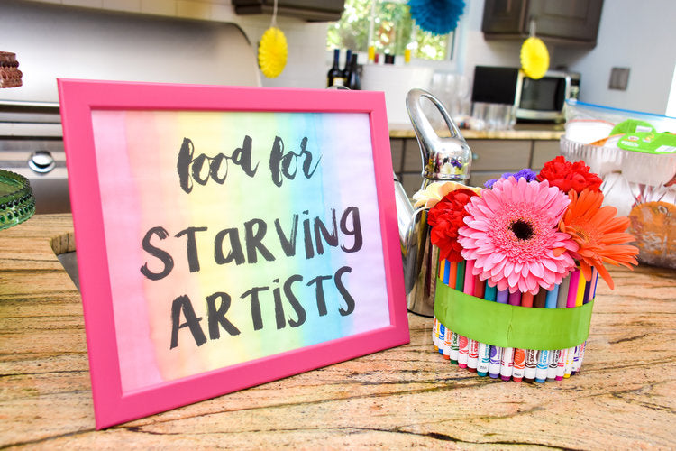 """Food for starving artists"" placard next to some daisies."
