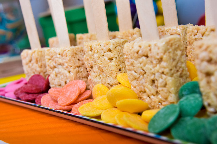 Rice crispy treats sitting in front of pink, red, orange, yellow, and green colored chocolate buttons