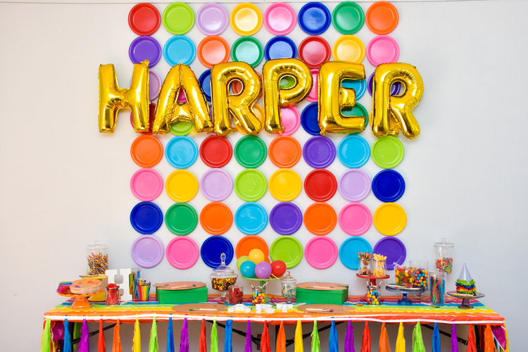 "Colorful candy jars on a table in front of a colorful wall with ""Harper"" mylar balloons hanging from it"