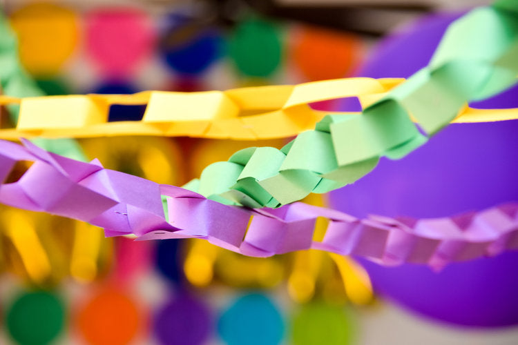 Closeup photo of yellow, lilac, and green paper ring garlands