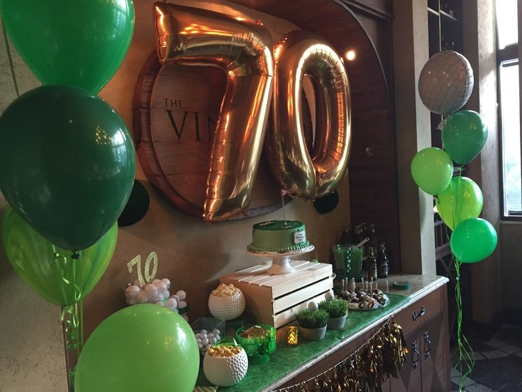 Decorated front wall with green latex balloons and gold mylar balloons saying 70