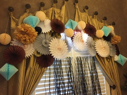 Brown, white, tan, and teal pinwheels and honeycomb paper decorations hanging around window