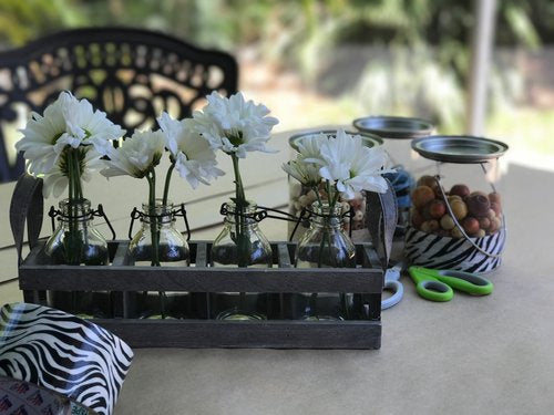 White daisies in tiny jars with snack jars in the background