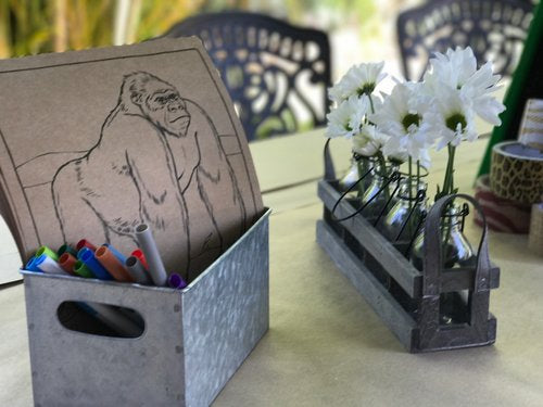 Closeup of activity box with gorilla drawing on craft paper with color pens.