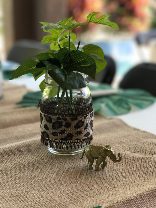 Closeup view of leafy table centerpiece in glass jar with tiny gold elephant sculpture