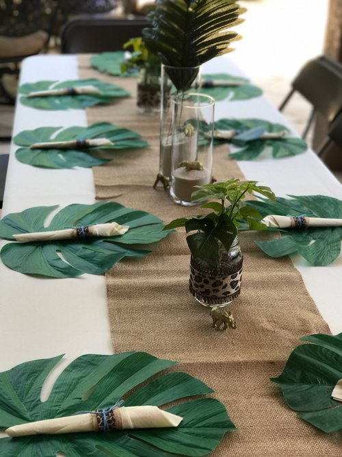 Overall view of table with multiple tropical leaf placesettings