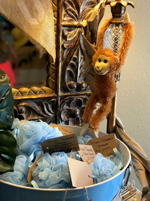 Closeup photo of stuffed monkey toy hanging over bucket of party favors
