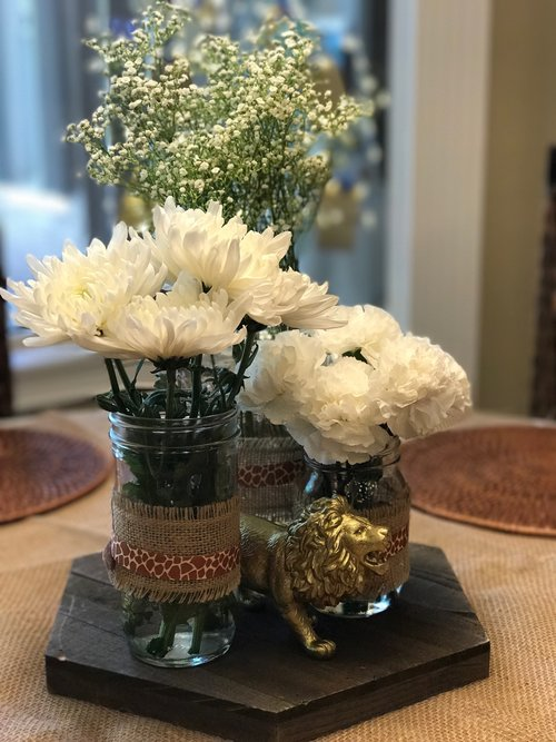 Vase table centerpiece holding white flowers with lion decoration