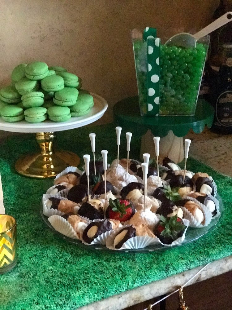 Closeup of tray of canolis, chocolate covered strawberries, green macarons, and green jellybeans