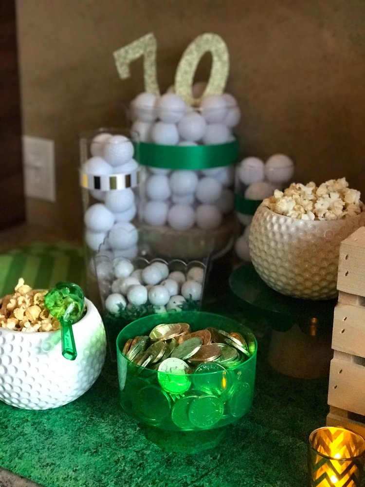 Closeup of golf ball themed bowls filled with popcorn and chocolate coins