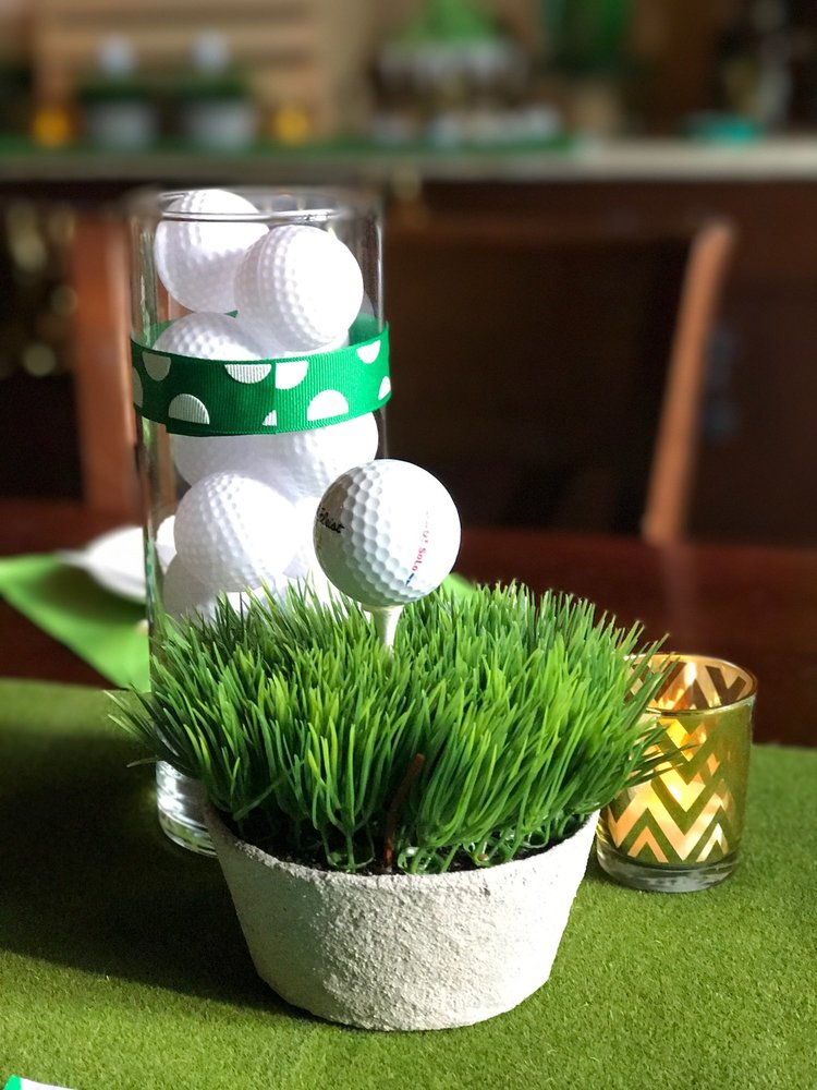 Closeup of table centerpiece of fake grass, golf tee, and golf balls