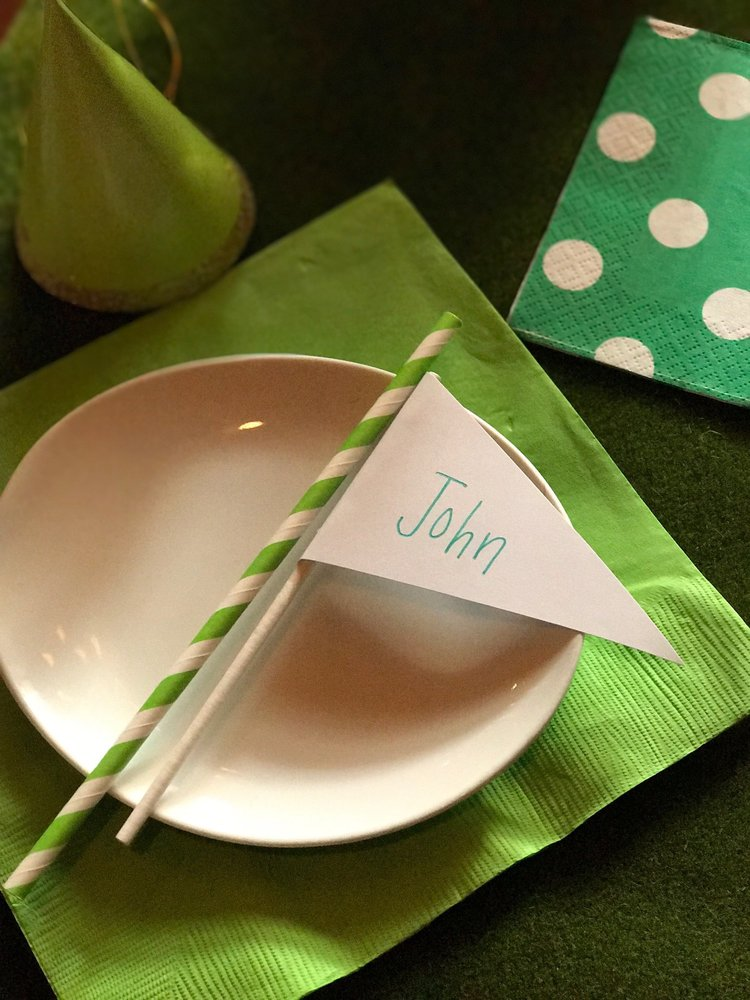 Closeup of place setting with green napkin and golf flag