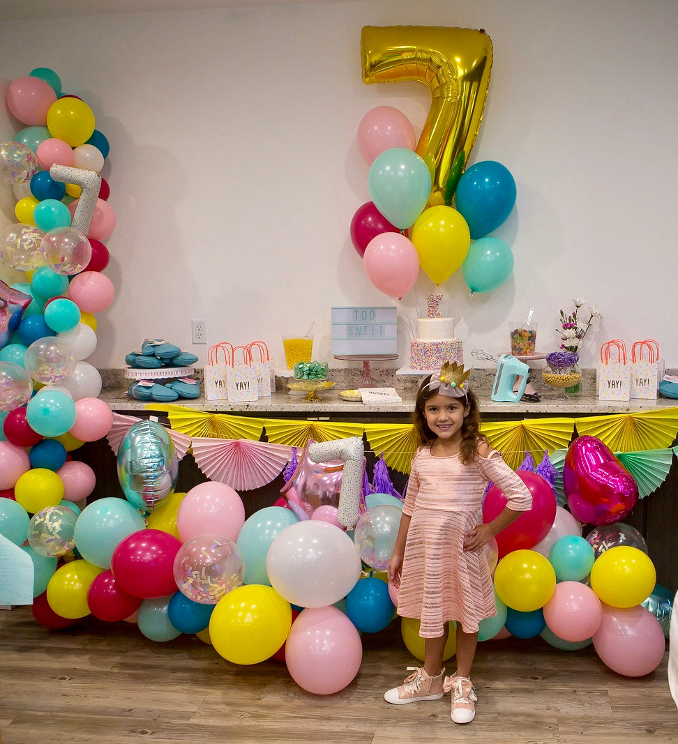 7 year old birthday girl posing in front of a balloon decorated table
