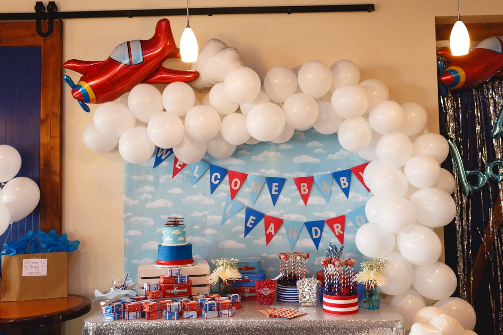 Wall decorated with plane balloons and a sky backdrop while a cake and snacks sit on a table in front of the decoration