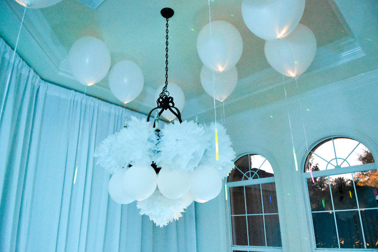 View of decorated chandelier with paper decorations surrounded by white latex balloons