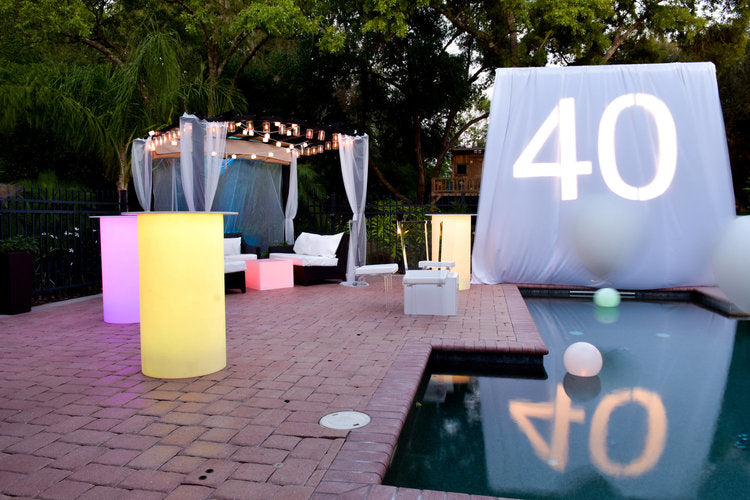 Pool view with various mood lighting around pool with a projected 40 on a white screen