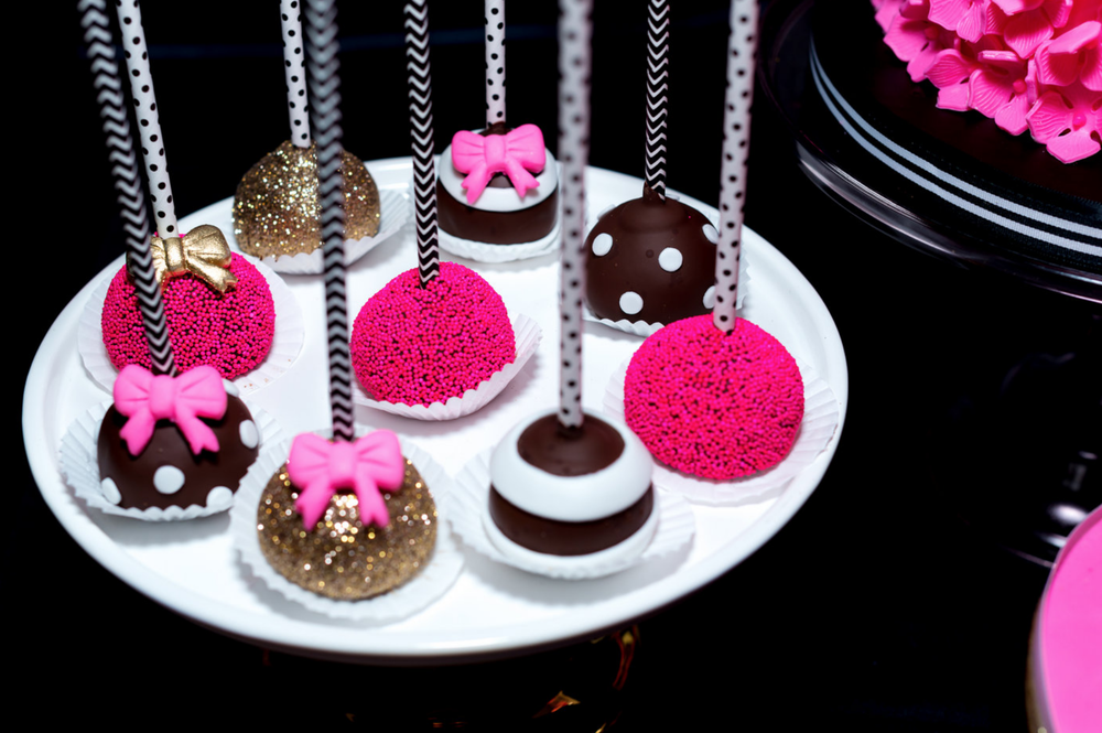 Closeup photo of various chocolate, pink, and sparkly cake pops