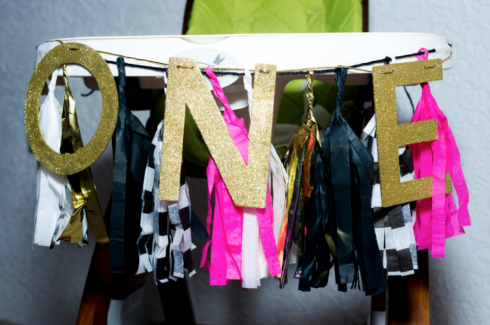 """One"" banner with pink/black/white tassel decorations"